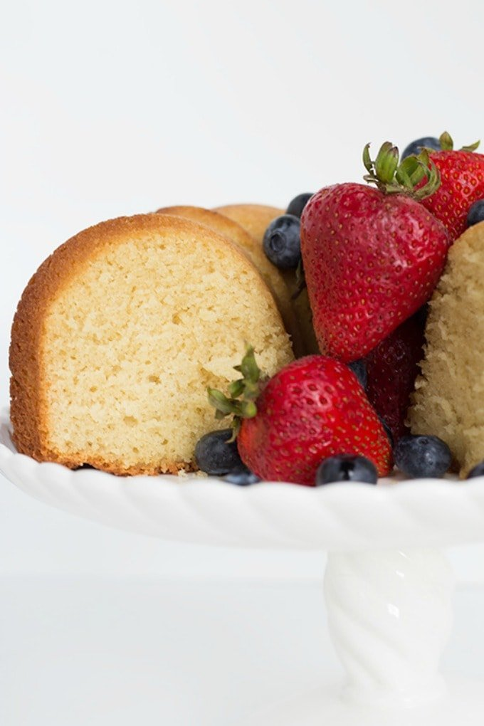 pound cake on a cake stand with a slice taken out