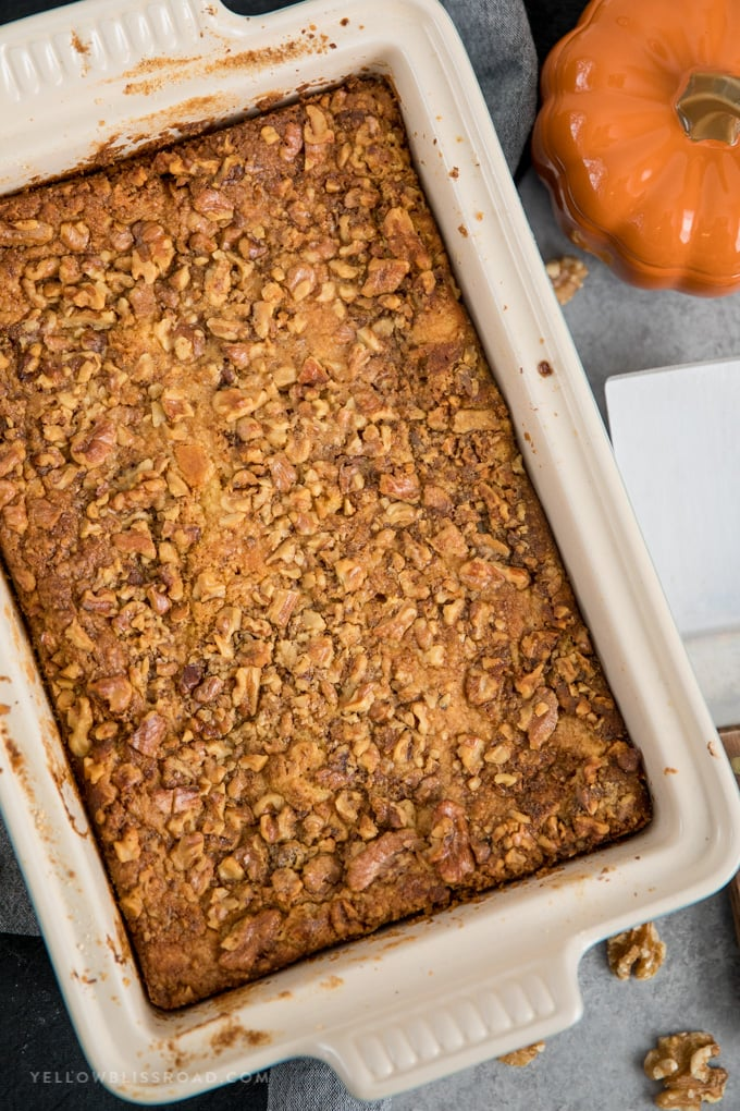 pumpkin dump cake with walnuts in a ceramic baking dish.