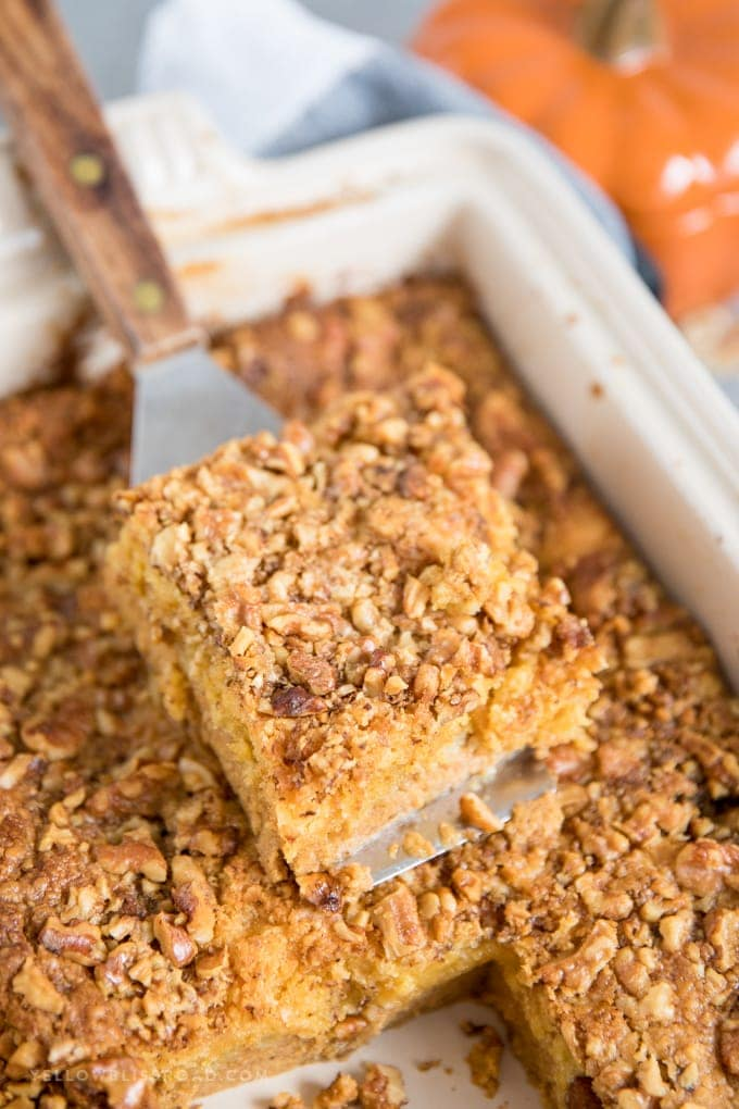 a slice of pumpkin dump cake on a spatula sitting on top of the whole cake.