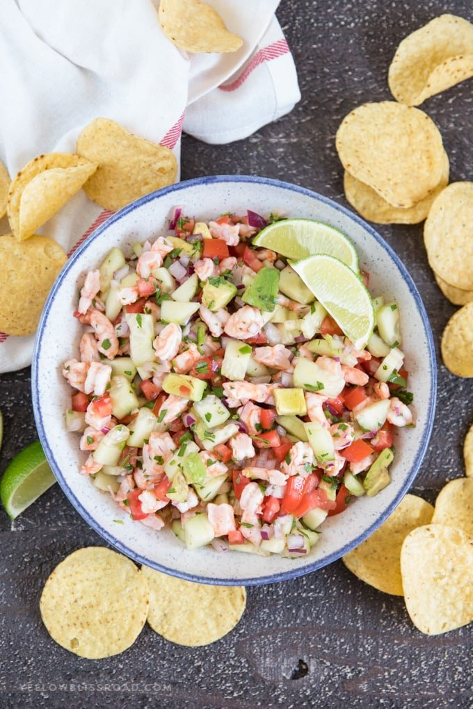 large bowl of shrimp ceviche surrounded by tortilla chips and lime wedges.