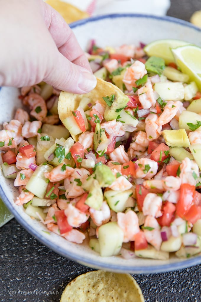 A tortilla chip dipping into a bowl of shrimp ceviche.