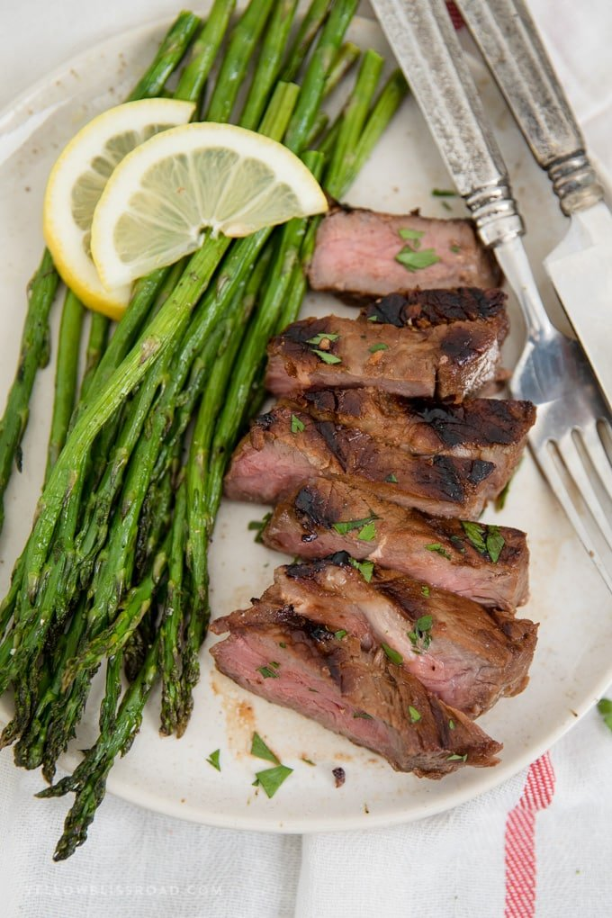 grilled steak in steak marinade, sliced on a plate with some asparagus, plus guide for grilling steak.