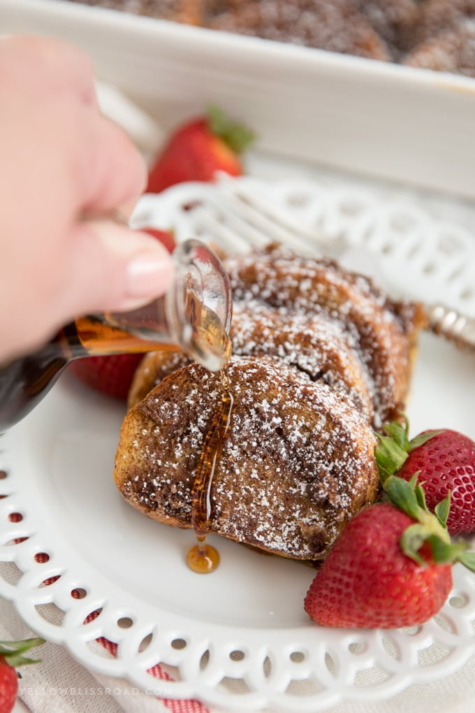 slices of overnight baked french toast with powdered sugar with syrup poured on top.