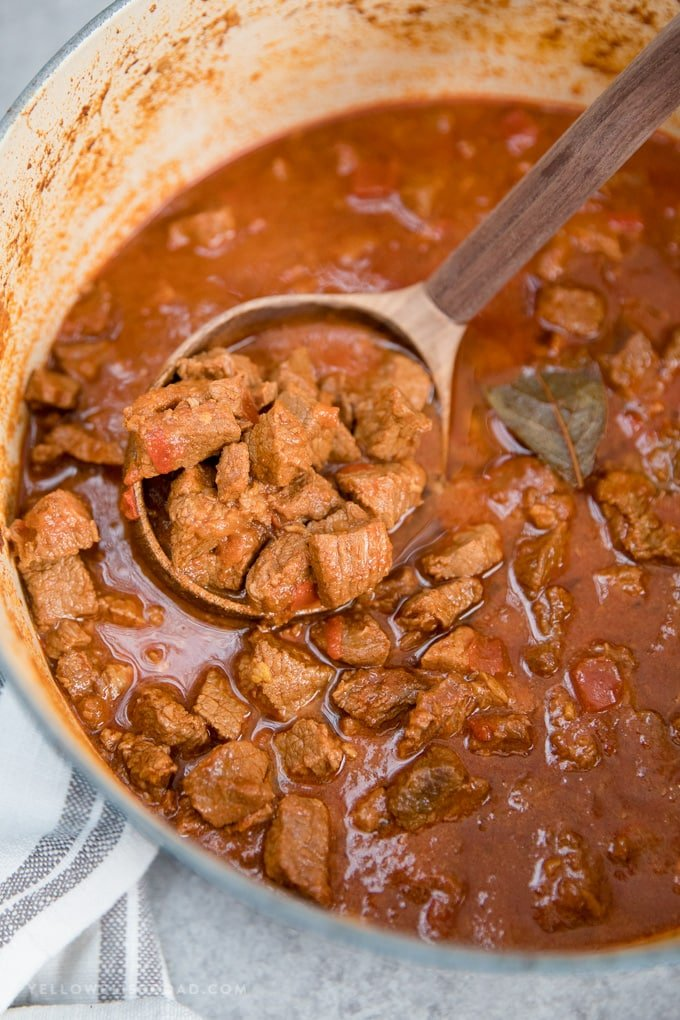Authentic Hungarian Goulash in a large pot with a wooden ladle.