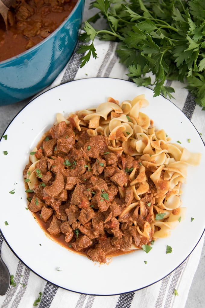 Hungarian goulash served on a plate over egg noodles.
