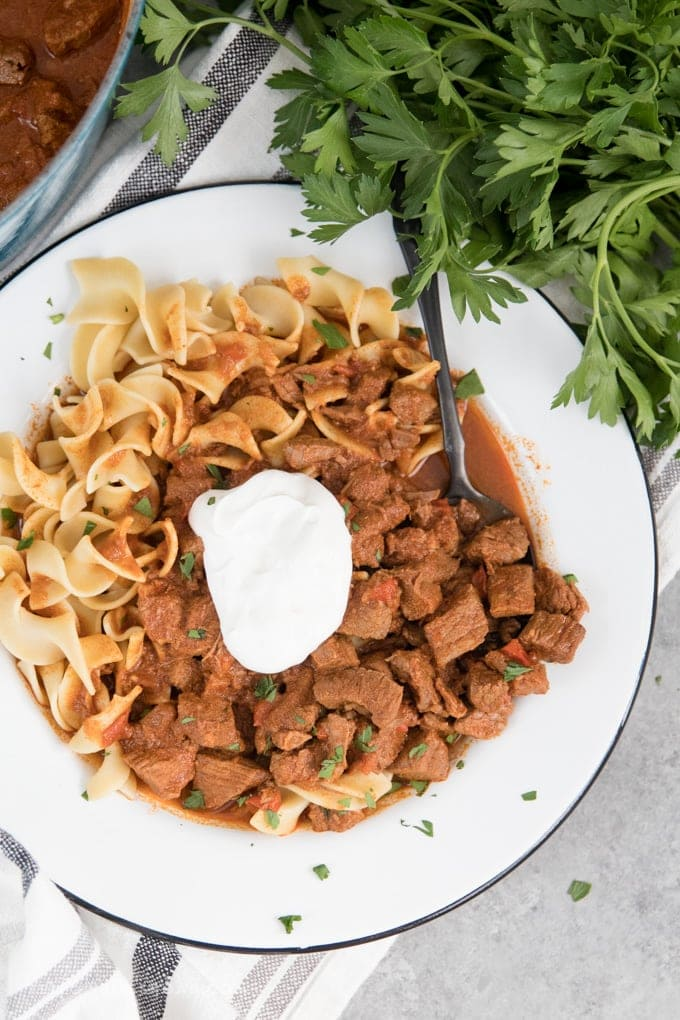 Authentic Hungarian Goulash with egg noodles and sour cream in a shallow white bowl with a black spoon.