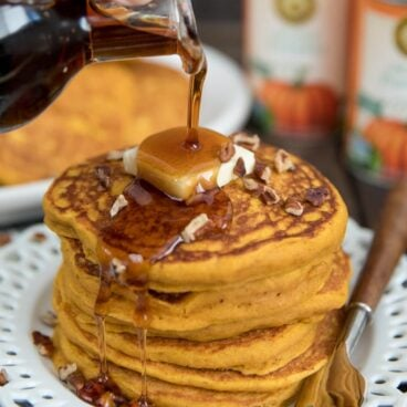 stack of pumpking pancakes on a white plate with butter and syrup pouring from a bottle.