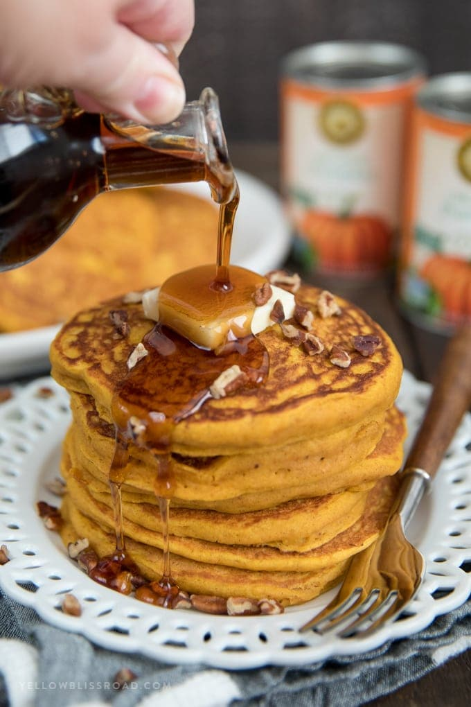 Maple syrup being poured over a stack of pumpkin pancakes with butter.