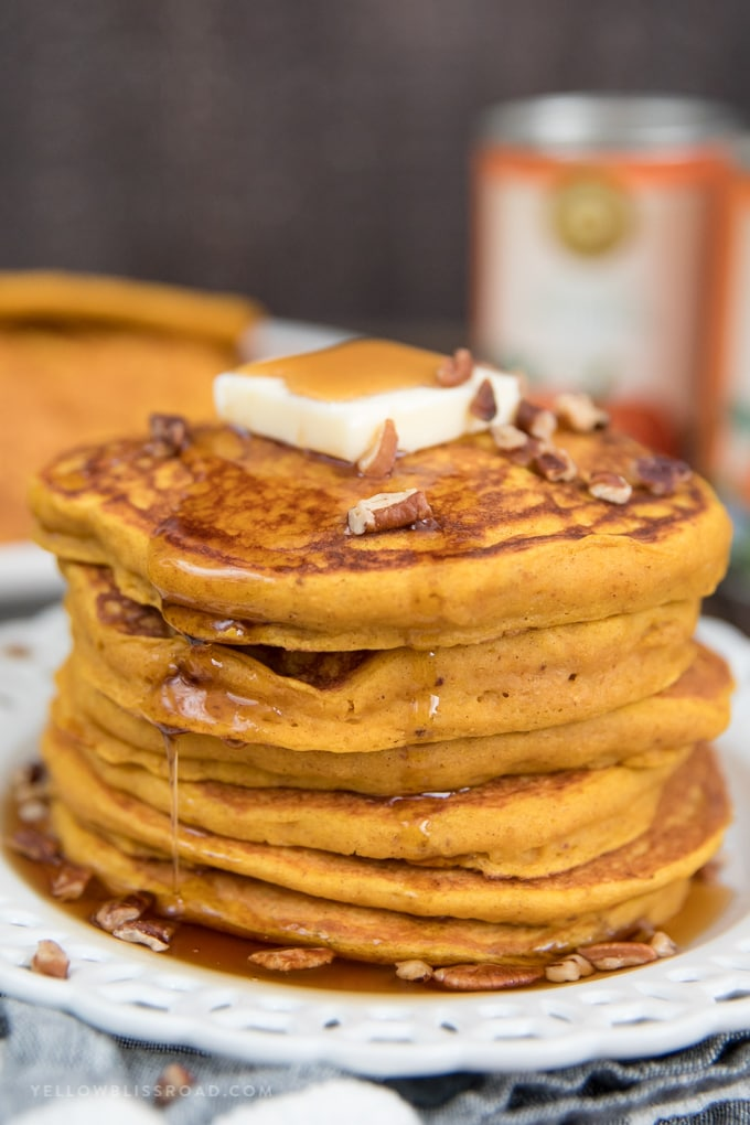 a stack of pumpkin pancakes with butter and syrup.