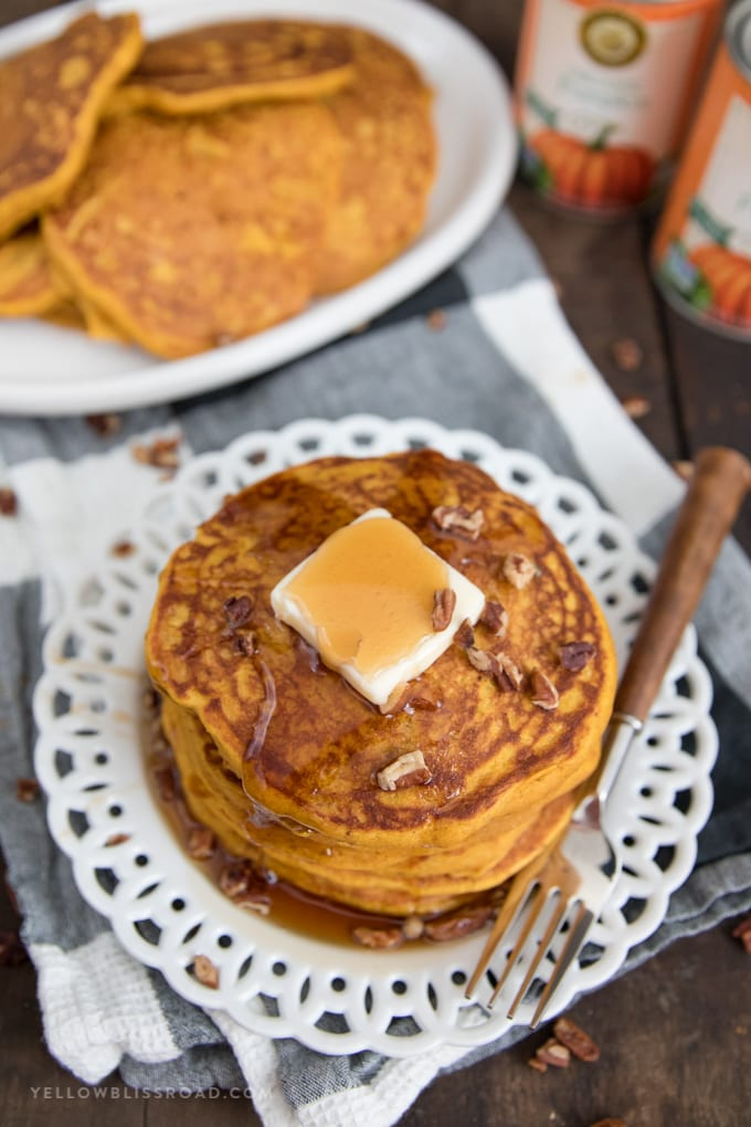 a plate of pumpkin pancakes with syrup and a fork.