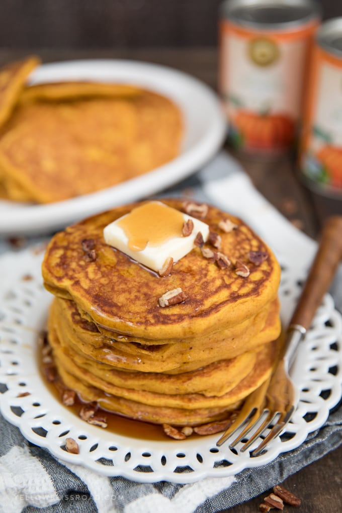 A plate of pumpkin pancakes with butter, pecans and syrup.