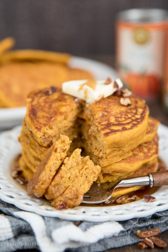 pumpkin pancakes on a plate with pieces on a fork.