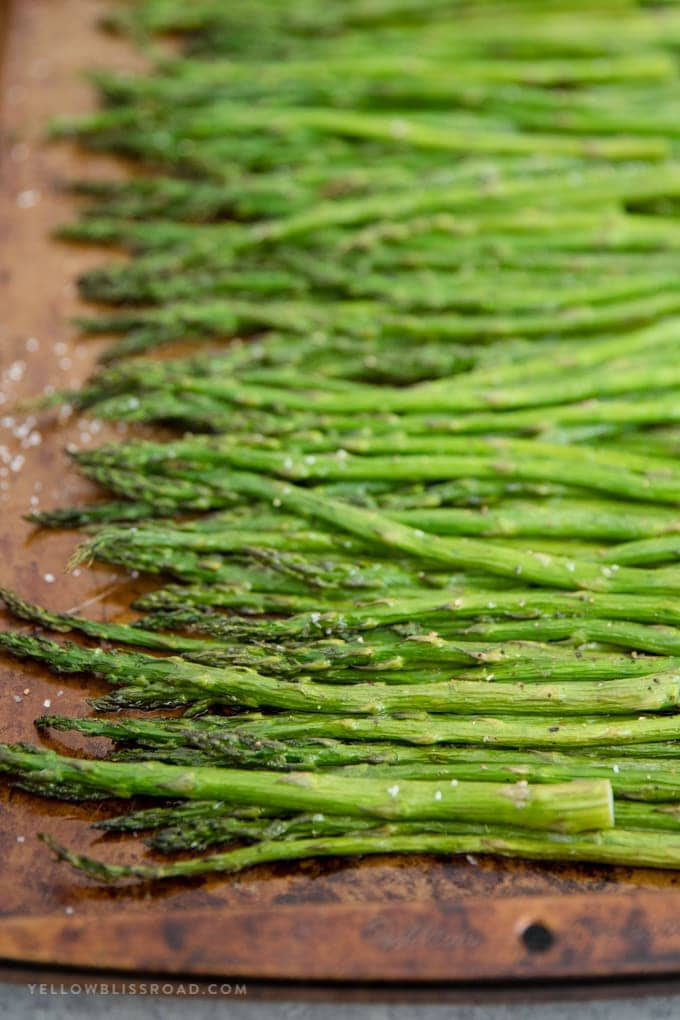 A close up image of roasted asparagus on a baking sheet