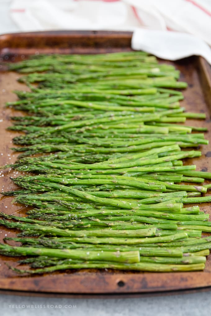 Easy oven roasted asparagus on a dark baking sheet.