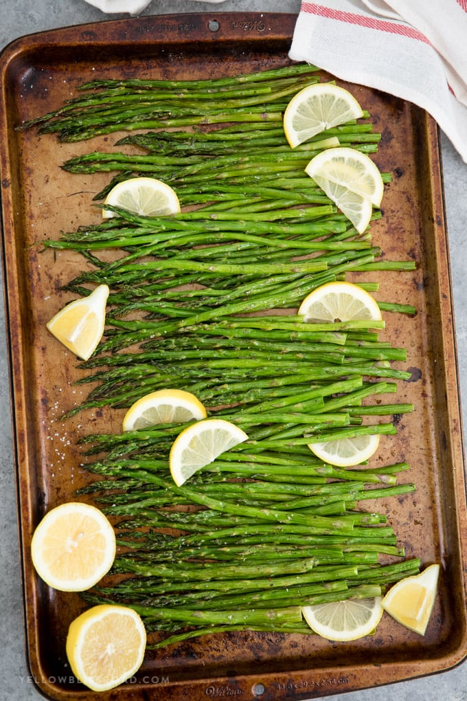 Easy oven roasted asparagus on a large baking sheet with lemon slices