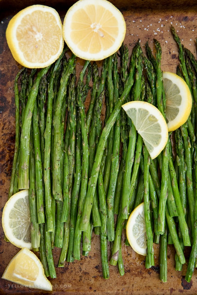 Easy oven roasted asparagus with lemons on a baking sheet.
