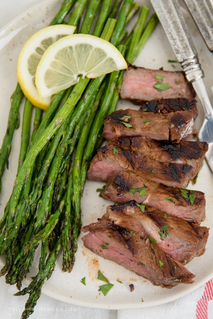 Oven roasted asparagus on a plate with sliced pieces of grilled steak.