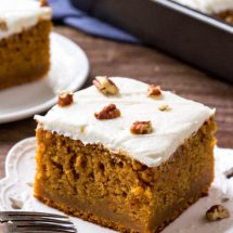 2 slices of sweet potato cake with marshmallow frosting and the pan of cake in the background.