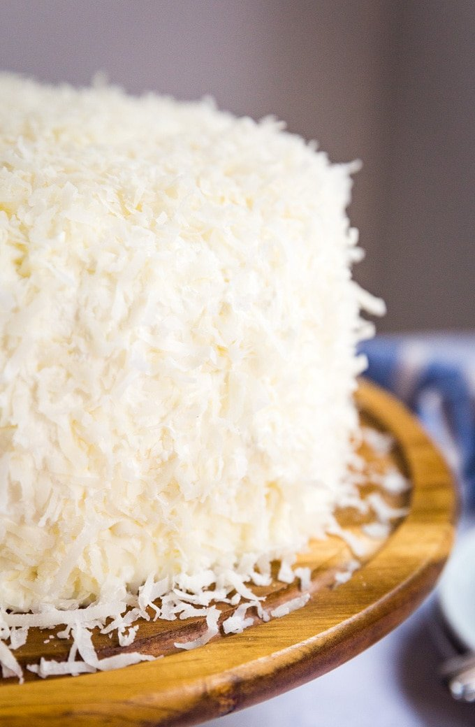 coconut cake with shredded coconut pressed onto the frosting all over the cake