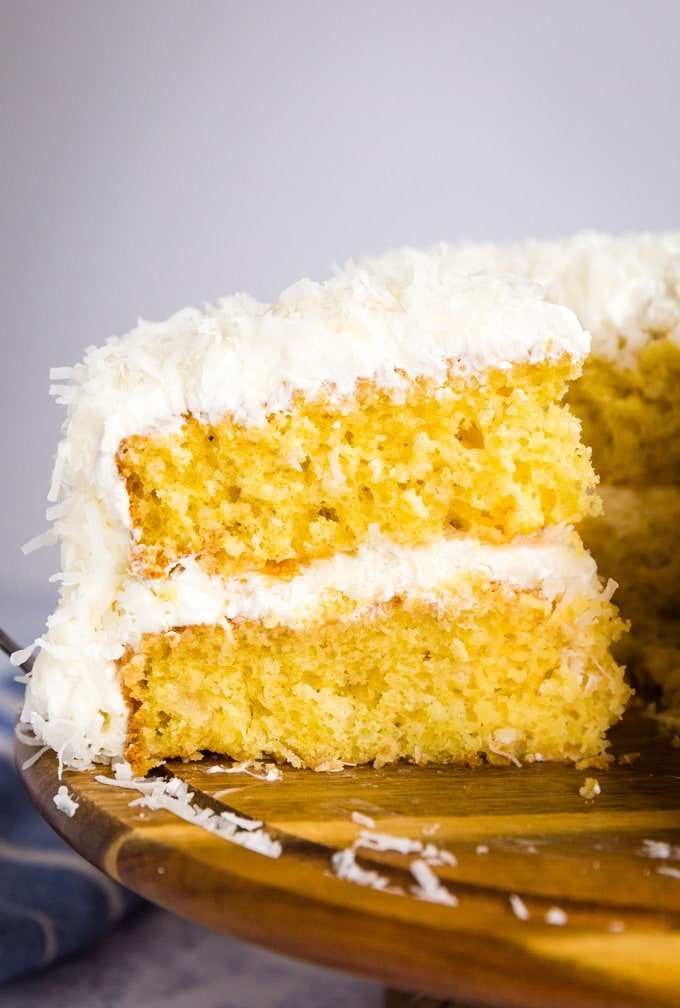 coconut cake slice being pulled away from the rest of the cake