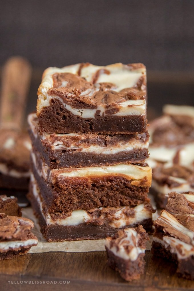 Cream Cheese Brownies stacked on top of each other.