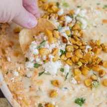 mexican street corn dip, a hand holding a tortilla chip, roasted corn, cotija cheese and cilantro on top. image for social media
