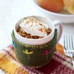 microwave apple crisp in a mug with whipped cream on top