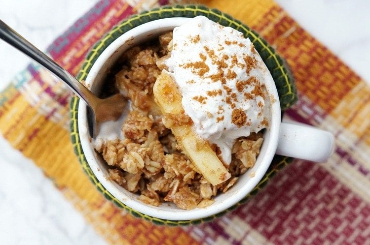 close up of microwave apple crisp in a mug with whipped cream, cinnamon, and oat topping