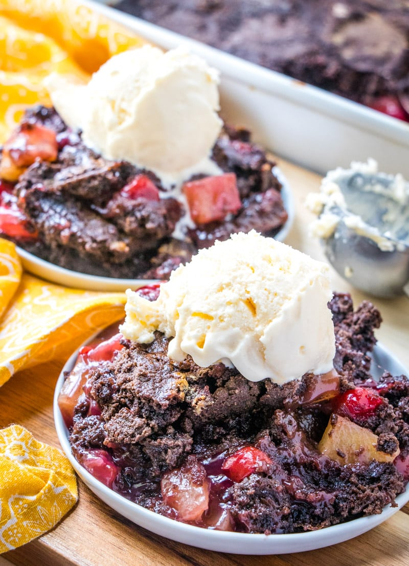 Two plates with servings of chocolate cherry dump cake topped with vanilla ice cream.