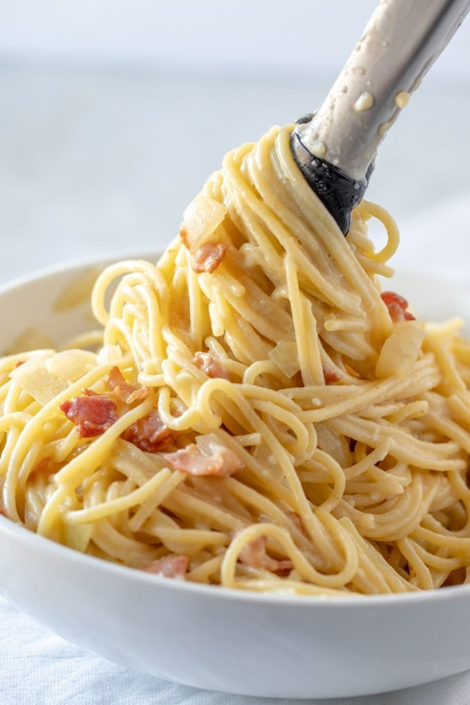 Pasta carbonara in a bowl with tongs twirling the spaghetti.
