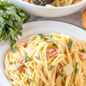 A plate of pasta with bacon and parmesan cheese