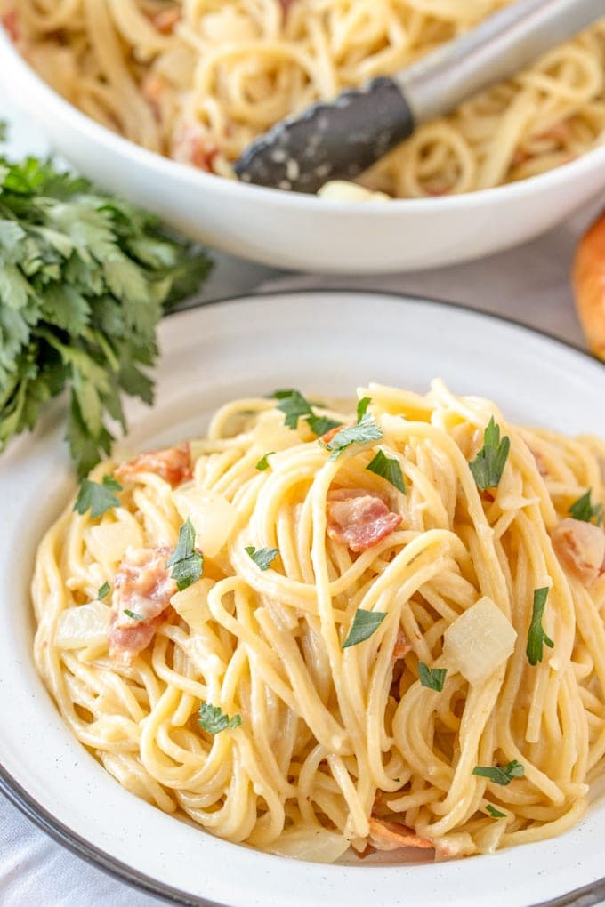 A plate of pasta carbonara with bacon and parsley.