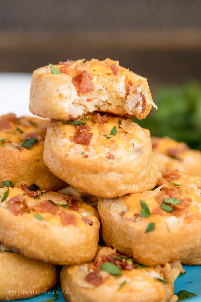 A stack of Baked Crack Chicken Pinwheels with a bite taken out of one.