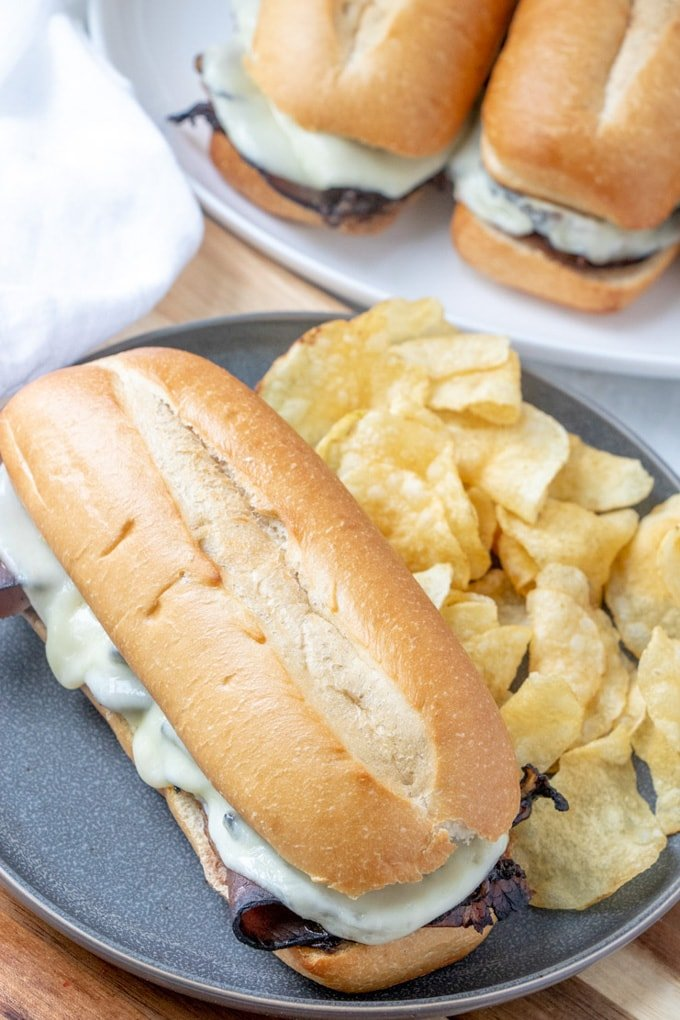 A french Dip Sandwich on a plate with potato chips