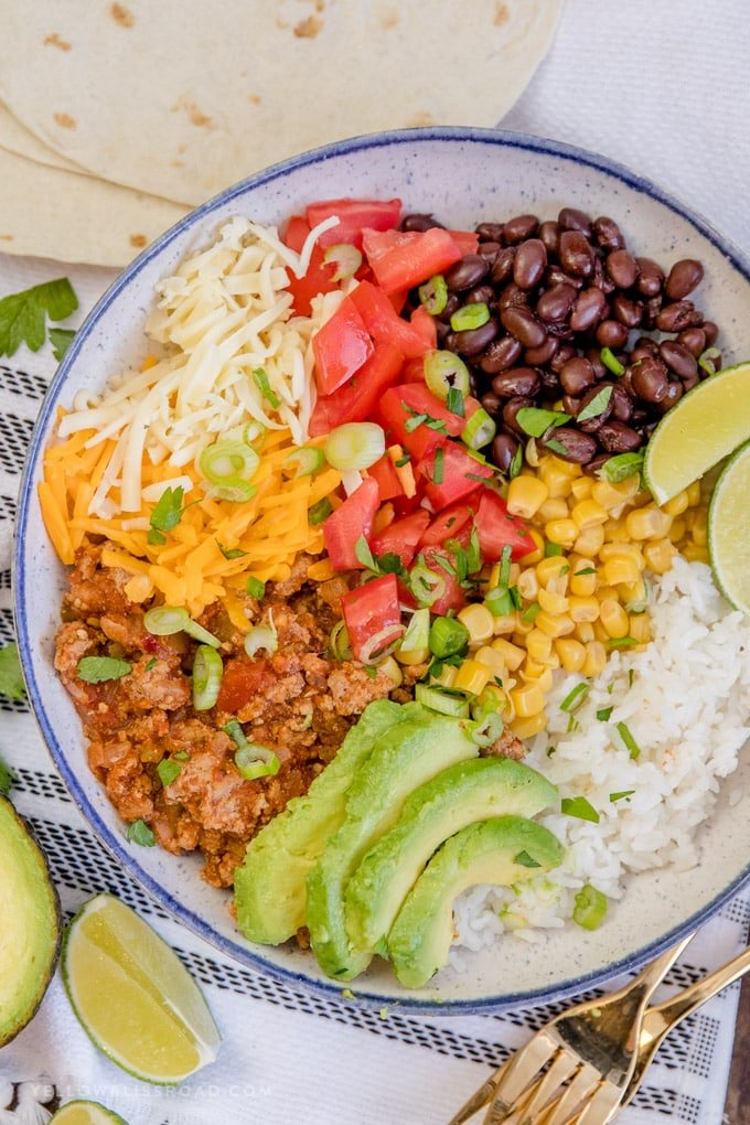 Turkey Taco Burrito Bowls are loaded with ground turkey taco meat, rice, black beans and a variety of toppings with tortillas on the side.