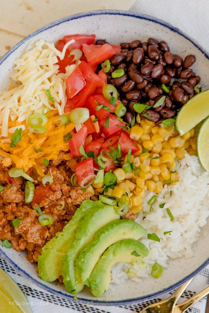 Turkey Taco Burrito Bowls are loaded with ground turkey taco meat, rice, black beans and a variety of toppings in a blue and white bowl.