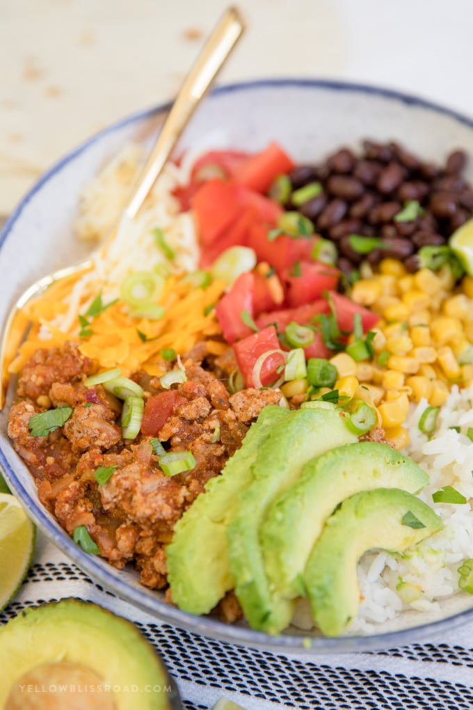 Turkey Taco Bowls - Ground turkey Taco meat, avocado, cheese, tomatoes and rice in a bowl.