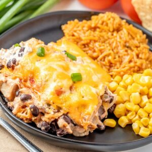 A plate filled with Mexican Chicken Casserole, rice, and corn.