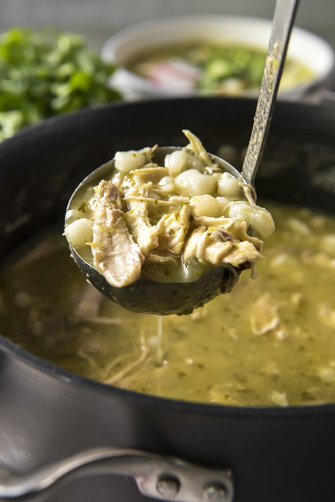 Ladle of Pozole Verde soup with chicken and hominy