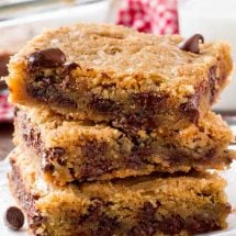 A stack of chocolate chip cookie bars with a glass of milk.