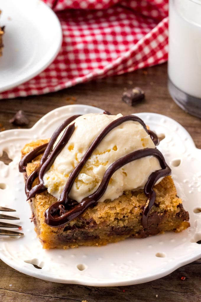 Chocolate chip cookie bars topped with ice cream and chocolate sauce.