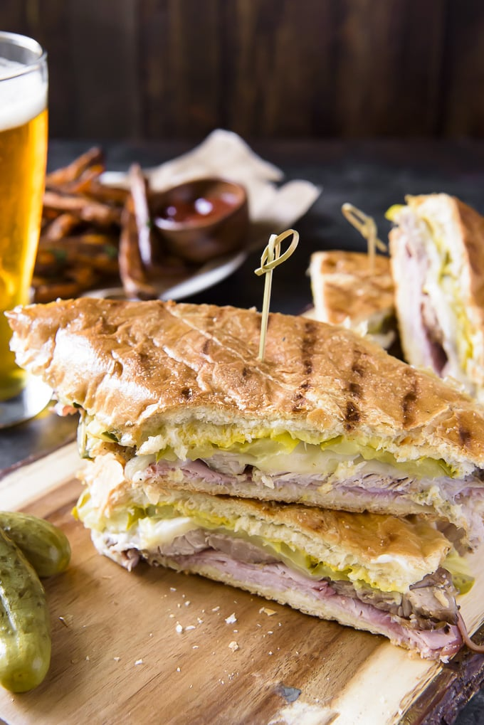 A Cuban Sandwich with a toothpick in it, a beer, fries and a pickle.