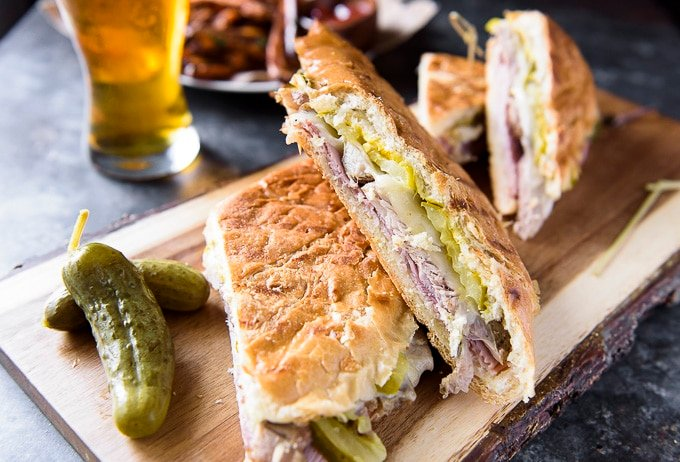 Two cuban sandwiches sitting on a wooden cutting board.