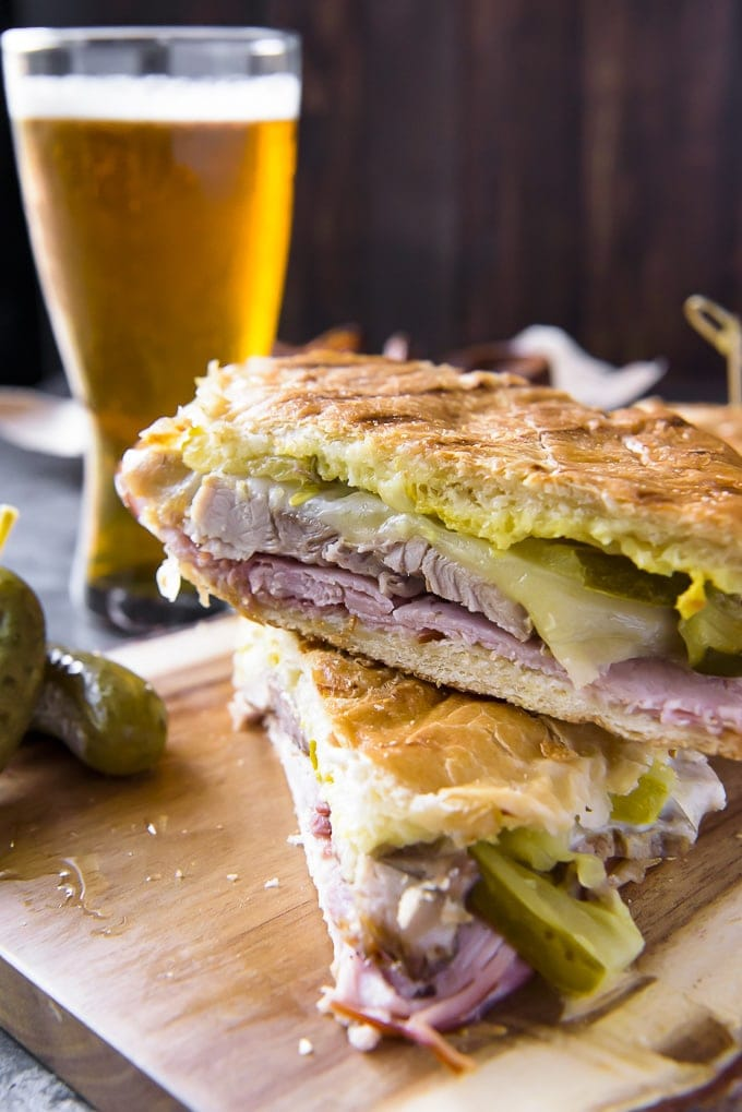 A close up of a cuban sandwich, showing the pork and ham with a glass of beer in the background.