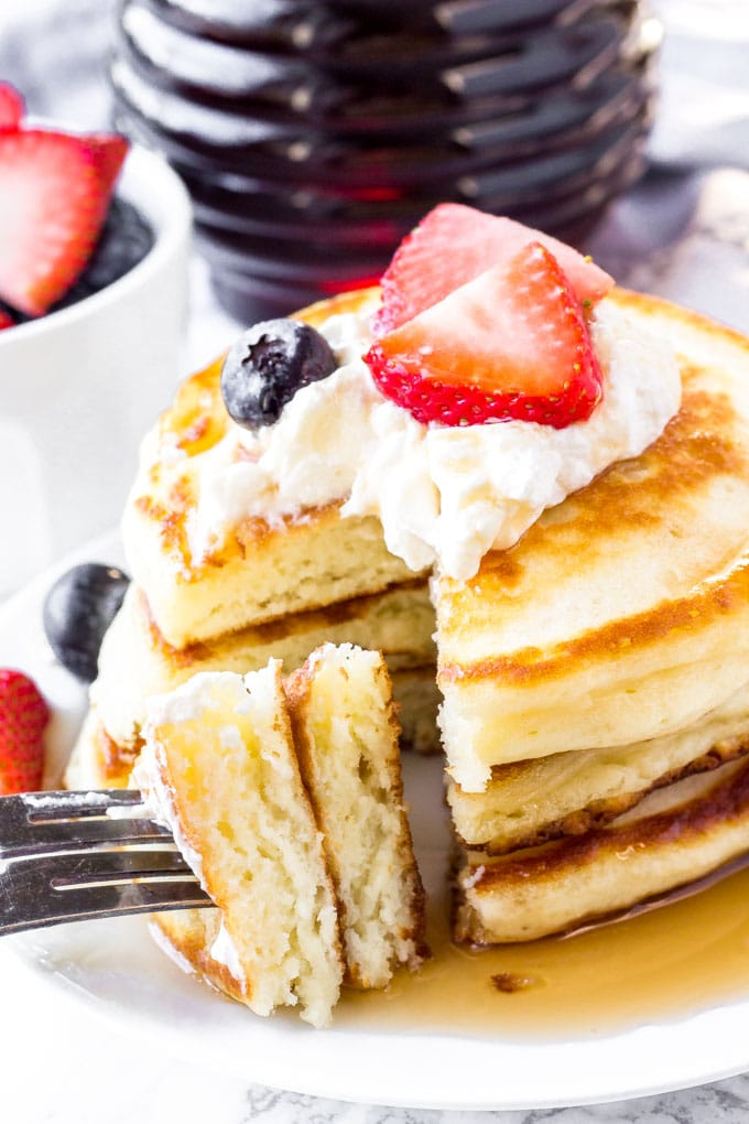 A stack of homemade pancakes with a bite taken out of it.