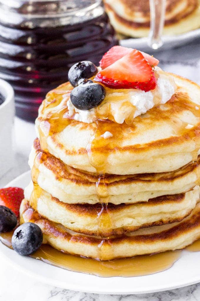 Stack of Greek yogurt pancakes topped with whipped cream, berries & syrup.