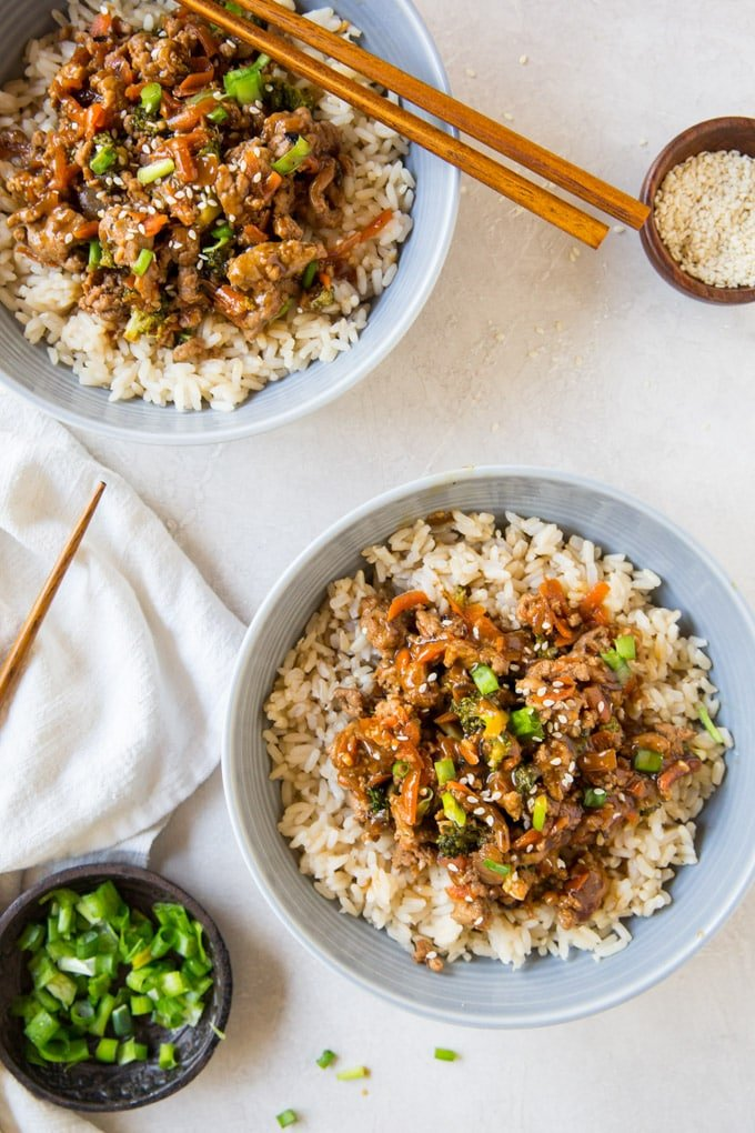 An overhead shot featuring two teriyaki turkey rice bowls, chopsticks, green onions and sesame seeds. (ground turkey recipes)