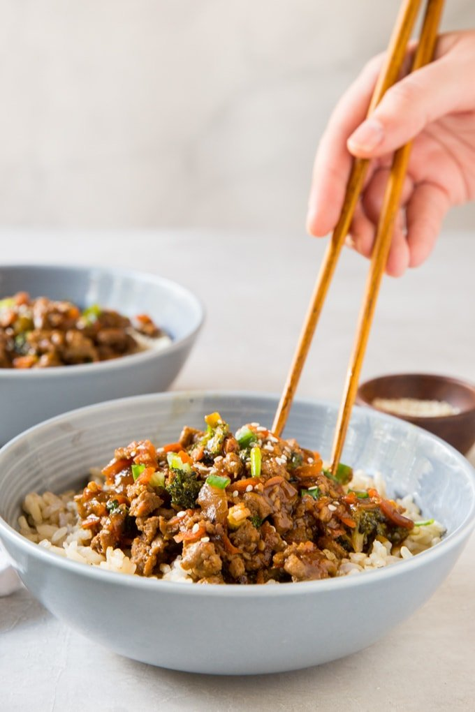 a hand with chopsticks, bowls with healthy ground turkey teriyaki, vegetables and rice