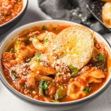 A bowl of soup with tomato broth, tortellini, spinach, cheese and parsley. A small piece on bread on top. Image created for social media.