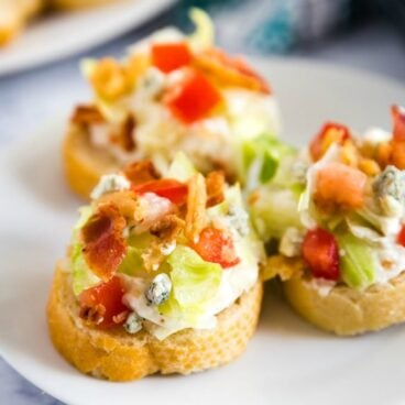 Crostini pieces with wedge salad dip on a plate.